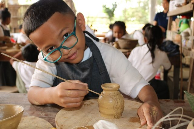Child decorating pottery